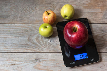 Big red apple on the scales