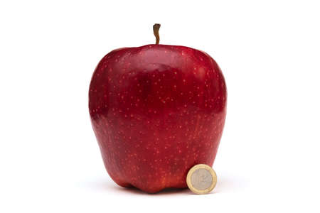 Big red apple on white background, size comparison with a coin