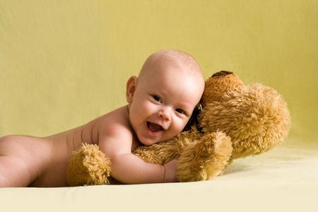 Portrait of the happy baby girl with teddy bear.