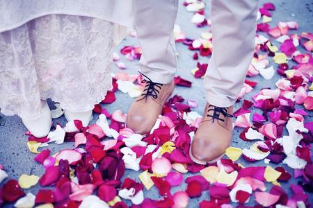 amongst: Bride and groom standing amongst rose petals