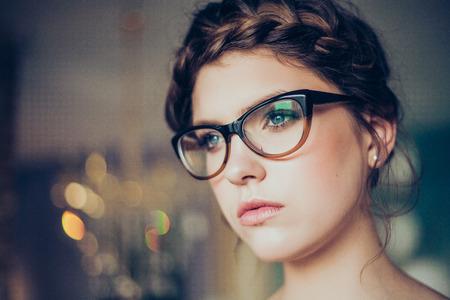 Retrato de mujer que llevaba bastante jóvenes gafas. Maquillaje profesional y peinado. Una piel perfecta. Foto de moda.