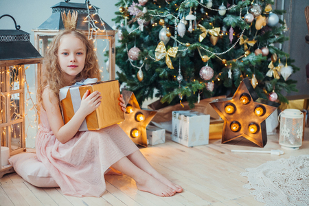 Happy little girl sitting under the Christmas tree and holding a gift box. Archivio Fotografico