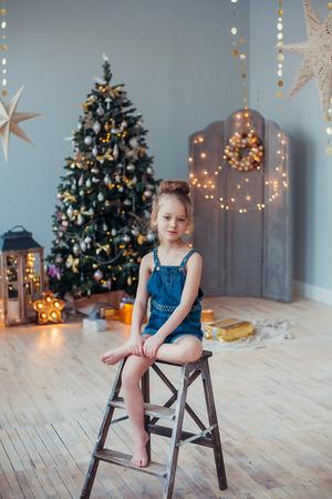 romper: Pretty little girl sitting in the living room near the Christmas tree.