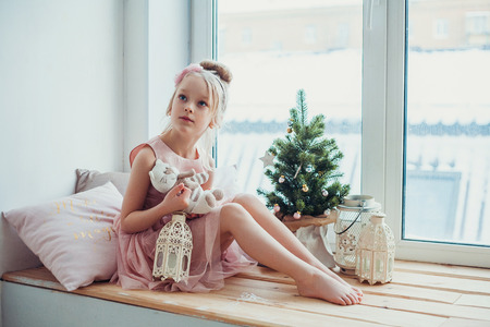 Adorable little girl sitting by the little Christmas tree.
