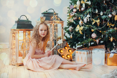 little girl dress: Happy little girl in a beautiful dress under the Christmas tree.   Stock Photo