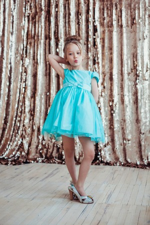 Little girl wearing mothers shoes. Fashion photo.