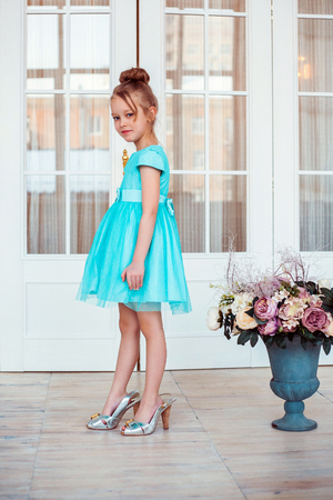 Little girl wearing mother's shoes. Fashion photo.