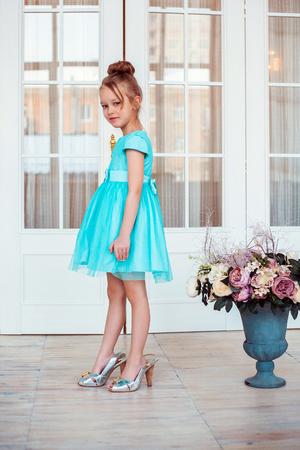 tacones: Niña que llevaba zapatos de la madre. Foto de moda.