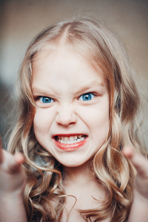 capricious: Portrait of angry capricious little girl shouting Stock Photo