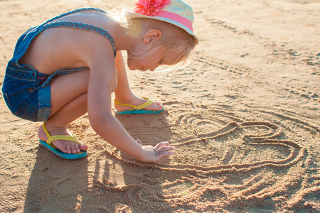 niñas jugando: Cute little girl playing with sand on the beach