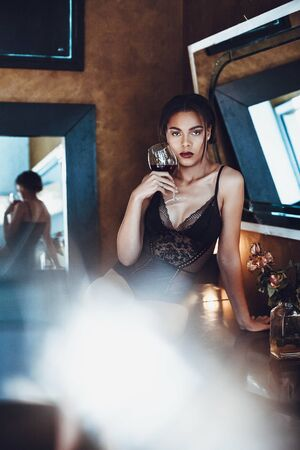 Beautiful young woman mixed race in seductive lingerie holding glass of red wine.