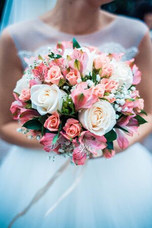 Close up photo of wedding bouquet in brides hands. Vertical image.