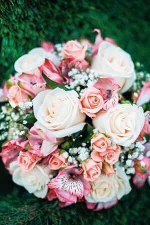 Close-up photo of traditional wedding bouquet lying on green grass. Vertical image.