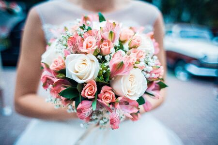 Close up photo of wedding bouquet in brides hands.