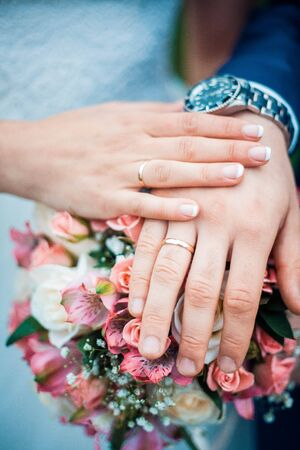 Closeup photo of hands of bride and groom with wedding rings and bouquet. Vertical image.