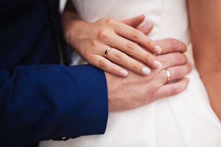 Close-up image of bride and grooms hands with wedding rings. Horizontal image.