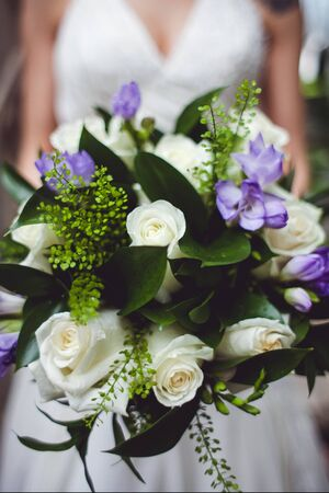 Close-up photo of wedding bouquet in brides hands. White and purple flowers. Vertical image. 写真素材