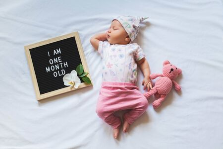 One month old baby girl wearing floral bodysuit and pink pants and laying down on white background. Shot from overhead.