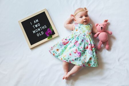 Two months old baby girl wearing floral dress laying down on white background and hugging knitted teddy bear.