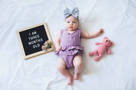 Three months old baby girl laying down on white background with letter board and teddy bear. Stock Photo
