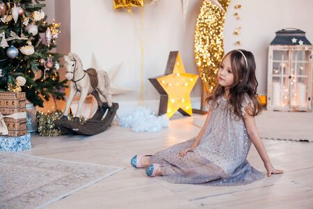 Pretty little girl sitting near Christmas tree indoors. 免版税图像