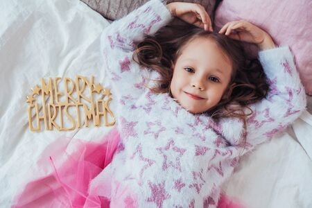 I love Christmas concept with cute child girl showing heart symbol. Imagens