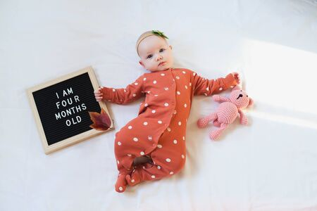 Four months old baby girl laying down on white background with letter board and teddy bear. Flat lay composition.