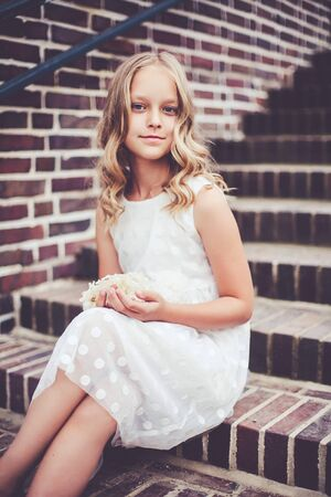 Fashion portrait of beautiful 9 -10 years old smiling girl sitting on the stairs.