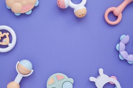 Flat lay composition with baby rattles set in pastel colors and space for text on lilac background.