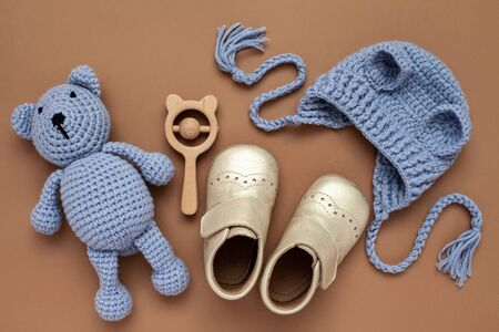 Flat lay composition with baby accessories set: crib shoes, teddy bear toy, knitted hat and wooden rattle. Archivio Fotografico