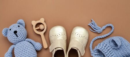 Flat lay banner with baby accessories set: crib shoes, teddy bear toy, knitted hat, wooden rattle and copy space.