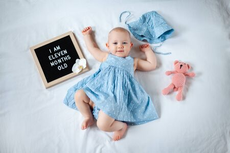 Eleven months old baby girl wearing blue dress laying down on white background with letter board and teddy bear. Archivio Fotografico