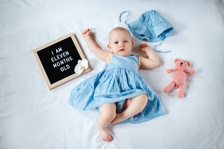 Eleven months old baby girl wearing blue summer dress laying down on white background with letter board and teddy bear.