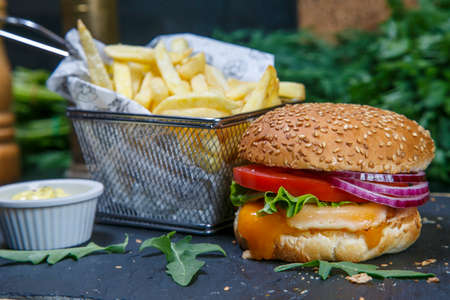 Black burger on a wooden background with potatoes and sauce Banque d'images - 115940291