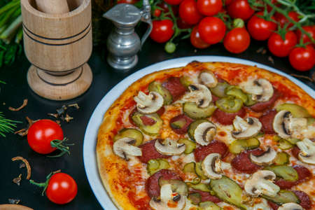 Pizza with ham, salami, cucumbers, olives, pineapple, tomato, peppers, cheese, mushrooms. Pizza on a white background. Fast food. Beautiful and cheesy Italian pizza.