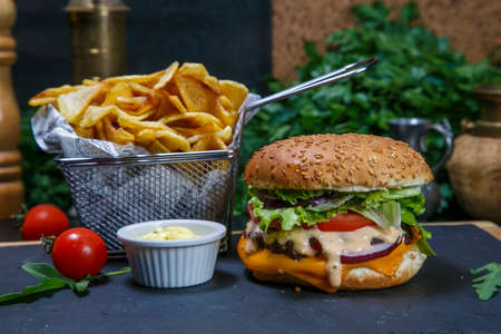 Black burger on a wooden background with potatoes and sauce Banque d'images - 115940366