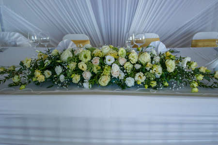 White and green bouquet on a stone parapet with rose, eustoma, chrysanthemum and dahlia. Horizontal closeup image Stock Photo