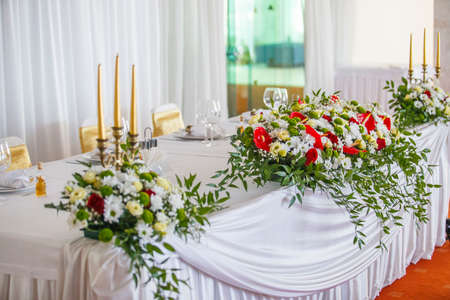 red and ivory floral arrangement prepared for reception, wedding table with candle and setting, winter concept