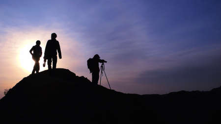 cameraman: Silhouette of photographers on the mountains at sunrise