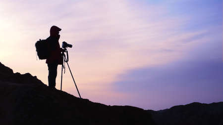 photographers: Silhouette of a photographer at sunrise Stock Photo