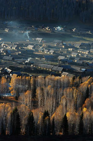 Landscape of a small village and woods in an autumn morning photo