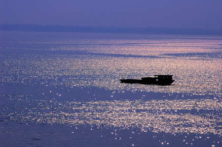 Silhouette of a filshing boat in lake at sunset photo