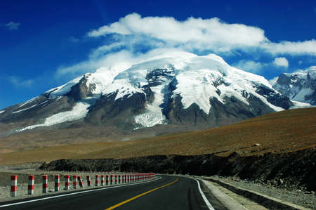Landscape of a highway extending to the snow mountains photo