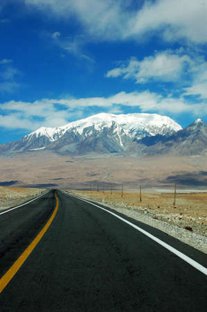 Landscape of a highway extending to the snow mountains Stock Photo - 8575785