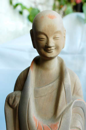 A sculpture of smiling buddha made of clay photo
