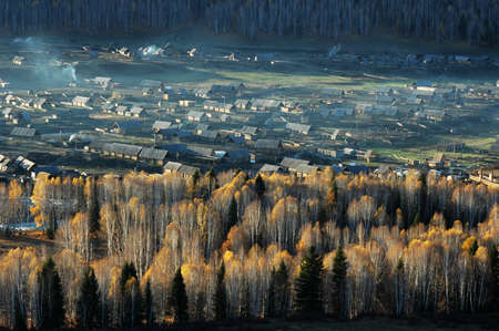 Landscape of a small village with woods in an autumn morning photo