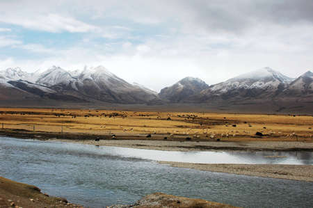 Landscape of snow mountains and stream in Tibet photo