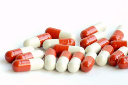 Closeup view of red-and-white medicine capsules on white background photo