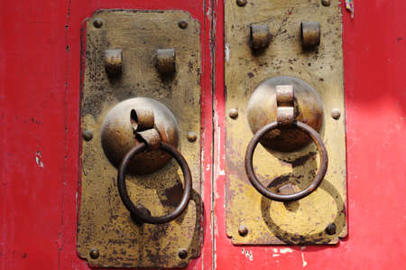 Copper doorknob or knockers on a red gate photo
