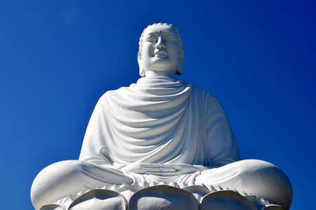 Closeup view of a historic buddha statue made of white marble against blue sky photo